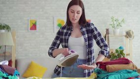 Η εύθυμη νέα γυναίκα στο πουκάμισο καρό σιδέρωσε το σίδηρο λινού στο σ απόθεμα βίντεο