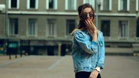 Η εύθυμη νέα ξανθή κυρία με τα κόκκινα χείλια χαμογελά στη κάμερα στην οδό απόθεμα βίντεο