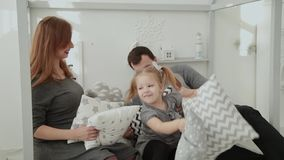 Η εύθυμη οικογένεια ρίχνει τα μαξιλάρια η μια στην άλλη στο νέο δωμάτιο έτους s απόθεμα βίντεο