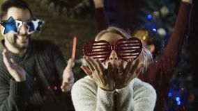 Η εύθυμη οικογένεια στα εορταστικά γυαλιά που φυσούν ακτινοβολεί απόθεμα βίντεο