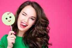 Η εύθυμη όμορφη γυναίκα που κρατά μια καραμέλα κλείνει το μάτι γέλια παρουσιάζει γλώσσα Κορίτσι Brunette μοντέρνο και μοντέρνο στ στοκ εικόνες