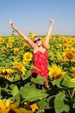 Η εύθυμη όμορφη γυναίκα στέκεται μεταξύ των ανθίζοντας ηλίανθων με τα αυξημένα χέρια μέχρι το σαφή μπλε ουρανό στοκ εικόνες με δικαίωμα ελεύθερης χρήσης