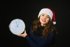 Η εύθυμη όμορφη νέα γυναίκα στο καπέλο Άγιου Βασίλη παρουσιάζει χρόνο Χριστουγέννων Στοκ εικόνα με δικαίωμα ελεύθερης χρήσης