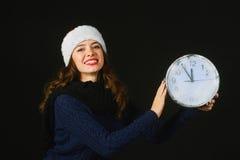 Η εύθυμη όμορφη νέα γυναίκα στο καπέλο Άγιου Βασίλη παρουσιάζει χρόνο Χριστουγέννων Στοκ φωτογραφία με δικαίωμα ελεύθερης χρήσης
