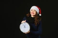 Η εύθυμη όμορφη νέα γυναίκα στο καπέλο Άγιου Βασίλη παρουσιάζει χρόνο Χριστουγέννων Στοκ Εικόνα
