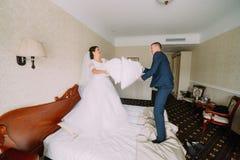 Η εύθυμοι νύφη και ο νεόνυμφος σε ένα δωμάτιο ξενοδοχείου συμμετέχουν στην πάλη μαξιλαριών Έννοια μήνα του μέλιτος Στοκ Εικόνες
