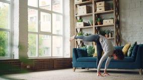 Η εύκαμπτη νέα γυναίκα ασκεί τα asanas γιόγκας στο σπίτι άσκησης στο πάτωμα του σύγχρονου σώματος τεντώματος διαμερισμάτων, όπλα  απόθεμα βίντεο