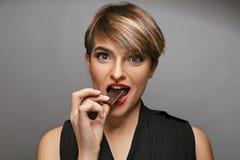 Η δελεαστική νέα κυρία επιθυμεί να θέσει στη κάμερα και να φάει την εύγευστη σοκολάτα σε ένα photostudio Στοκ Φωτογραφία