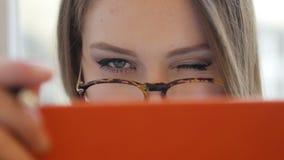 Η δελεαστική flirty ντροπαλή νέα ξανθή γυναίκα στα γυαλιά κάλυψε το πρόσωπό της από στενό τον επάνω βιβλίων φιλμ μικρού μήκους