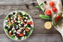 Η ελληνικά σαλάτα και τα συστατικά, επίπεδες βάζουν Στοκ φωτογραφία με δικαίωμα ελεύθερης χρήσης