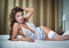 Η ελκυστική γυναίκα προκλητικό άσπρο lingerie που βρίσκεται στο σαγηνευτικό θέτει στο κρεβάτι Brunette με το προκλητικό σώμα Πορτ Στοκ Εικόνα