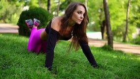 Η ελκυστική γυναίκα brunette που κάνει την ώθηση workout επάνω ασκεί στη χλόη στο πάρκο Ώθηση UPS με τα γόνατα Σε αργή κίνηση πυρ απόθεμα βίντεο