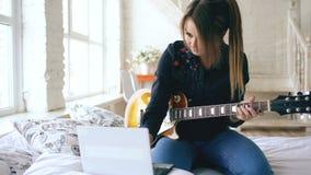 Η ελκυστική εκμάθηση νέων κοριτσιών να παίζουν την ηλεκτρική κιθάρα με το σημειωματάριο κάθεται στο κρεβάτι στην κρεβατοκάμαρα στ απόθεμα βίντεο