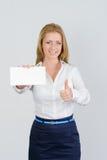 Η ελκυστική επιχειρηματίας παρουσιάζει τον αντίχειρα και κενή επαγγελματική κάρτα Στοκ Εικόνες