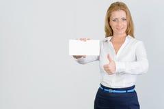 Η ελκυστική επιχειρηματίας παρουσιάζει τον αντίχειρα και κενή επαγγελματική κάρτα Στοκ Φωτογραφία