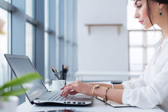 Η ελκυστική θηλυκή βοηθητική εργασία, δακτυλογράφηση, που χρησιμοποιεί το φορητό υπολογιστή, συγκεντρώθηκε, εξετάζοντας το όργανο στοκ εικόνες