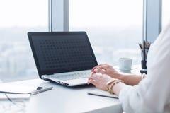 Η ελκυστική θηλυκή βοηθητική εργασία, δακτυλογράφηση, που χρησιμοποιεί το φορητό υπολογιστή, συγκεντρώθηκε, εξετάζοντας το όργανο στοκ εικόνες με δικαίωμα ελεύθερης χρήσης