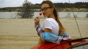 Η ελκυστική κυρία με τα κόκκινα χείλια και τα γυαλιά ηλίου γλείφει ένα lollipop απόθεμα βίντεο