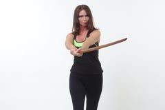 Η ελκυστική μέσης ηλικίας γυναίκα στο αθλητικό εργαλείο που κρατά το α ή ξύλινο ξίφος Στοκ Φωτογραφία