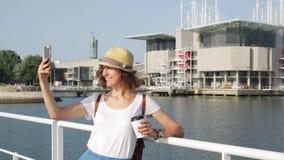 Η ελκυστική νέα γυναίκα κάνει τη φωτογραφία κοντά στη Λισσαβώνα Oceanarium κοντά στον ποταμό Tagus απόθεμα βίντεο