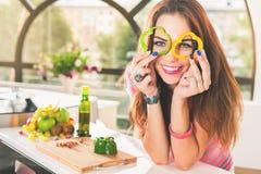 Η ελκυστική νέα γυναίκα κρατά τα φρέσκα κομμάτια του πιπεριού κουδουνιών Στοκ Εικόνες