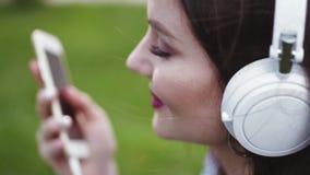 Η ελκυστική νέα γυναίκα με το φως makeup και τα κόκκινα χείλια ακούει τη μουσική στο έξυπνο τηλέφωνο, και τραγουδά συναισθηματικά φιλμ μικρού μήκους