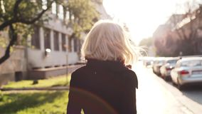 Η ελκυστική νέα γυναίκα σε ένα μαύρο παλτό περπατά κάτω από την εγκαταλειμμένη οδό άνοιξη, στροφές στη κάμερα και δίνει έναν όμορ φιλμ μικρού μήκους