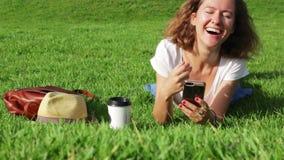Η ελκυστική νέα γυναίκα στο χορτοτάπητα χρησιμοποιεί ένα smartphone στην ηλιόλουστη ημέρα απόθεμα βίντεο