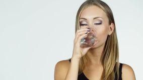 Η ελκυστική ξανθή γυναίκα πίνει το νερό σε ένα άσπρο υπόβαθρο απόθεμα βίντεο