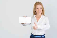 Η ελκυστική ξανθή επιχειρηματίας παρουσιάζει τον αντίχειρα και κενή επαγγελματική κάρτα Στοκ Φωτογραφία