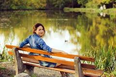 Η ελκυστική συνεδρίαση κοριτσιών σε έναν πάγκο Στοκ Εικόνες