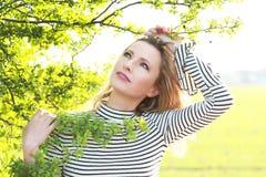 Η ελκυστική ώριμη γυναίκα με πράσινο βγάζει φύλλα το εξωτερικό Στοκ Φωτογραφία
