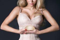 Η ζάλη της ξανθής γυναίκας κρατά στα μοσχεύματα σιλικόνης χεριών της στοκ εικόνες