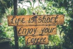 Η ζωή είναι σύντομη απολαμβάνει το κείμενο καφέ σας σε ένα ξύλινο πιάτο στους τροπικούς κύκλους του νησιού του Μπαλί, Ινδονησία στοκ φωτογραφία