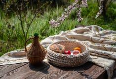 Η ζωή Πάσχας ακόμα ως κανάτα και πλεκτός pottle με το χρωματισμένο εσωτερικό αυγών μένει στον ηλικίας ξύλινο πίνακα με το τραπεζο στοκ εικόνες με δικαίωμα ελεύθερης χρήσης