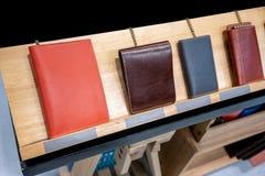 Η ζωηρόχρωμη επίδειξη πορτοφολιών δέρματος σε ξύλινο τοποθετεί σε ράφι στο κατάστημα στοκ εικόνες