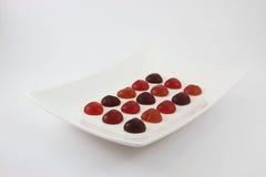 Η ζωηρόχρωμη ζελατίνα μορφής καρδιών τακτοποιείται στο άσπρο πιάτο Στοκ Φωτογραφία