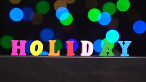 Η ζωηρόχρωμη λέξη ` διακοπές ` από τις πολύχρωμες ξύλινες επιστολές μπροστά από την περίληψη θόλωσε το υπόβαθρο φω'των bokeh φιλμ μικρού μήκους