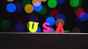 Η ζωηρόχρωμη λέξη ` ΗΠΑ ` από τις πολύχρωμες ξύλινες επιστολές μπροστά από την περίληψη θόλωσε το υπόβαθρο φω'των bokeh φιλμ μικρού μήκους