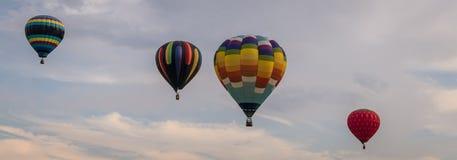 Η ζωηρόχρωμη σειρά μπαλονιών ζεστού αέρα επιπλέει μέσω του ουρανού στο σούρουπο στην έκθεση της Farmer ` s κομητειών του Warren σ Στοκ Εικόνες