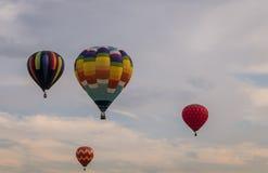 Η ζωηρόχρωμη σειρά μπαλονιών ζεστού αέρα επιπλέει μέσω του ουρανού στο σούρουπο στην έκθεση της Farmer ` s κομητειών του Warren σ Στοκ Φωτογραφίες