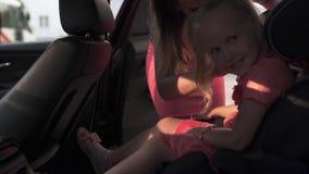 Η ζώνη ασφαλείας ασφάλειας στερεώνει το κάθισμα αυτοκινήτων παιδιών με τη μητέρα και την κόρη Νέο καυκάσιο άσπρο mom που φορά θερ φιλμ μικρού μήκους
