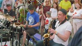 Η ζώνη τζαζ οδών αποδίδει στην οδό στα τύμπανα και το σκεπάρνι παιχνιδιού ημέρας πόλεων φιλμ μικρού μήκους