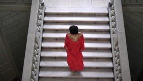 Η ηθοποιός σε ένα κομψό κόκκινο φόρεμα στα υψηλά τακούνια κατεβαίνει τη μεγάλη σκάλα σε ένα όμορφο δωμάτιο και κοιτάζει έπειτα απόθεμα βίντεο