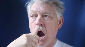 Ηληκιωμένος που βουρτσίζει τα δόντια του απόθεμα βίντεο