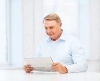 Ηληκιωμένος που διαβάζει στο σπίτι την εφημερίδα Στοκ Εικόνες