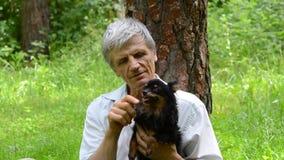 Ηληκιωμένος που κρατά ένα μικρό σκυλί φιλμ μικρού μήκους