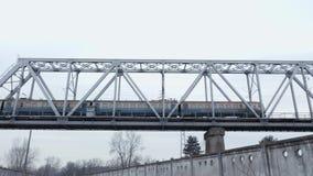 Η ηλεκτρική επιβατική αμαξοστοιχία διασχίζει μια γέφυρα σιδηροδρόμων φιλμ μικρού μήκους
