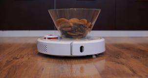 Η ηλεκτρική σκούπα ρομπότ φέρνει ένα πιάτο των γλυκών φιλμ μικρού μήκους