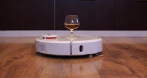 Η ηλεκτρική σκούπα ρομπότ φέρνει ένα ποτήρι του κονιάκ από τα δεξιά πρ απόθεμα βίντεο